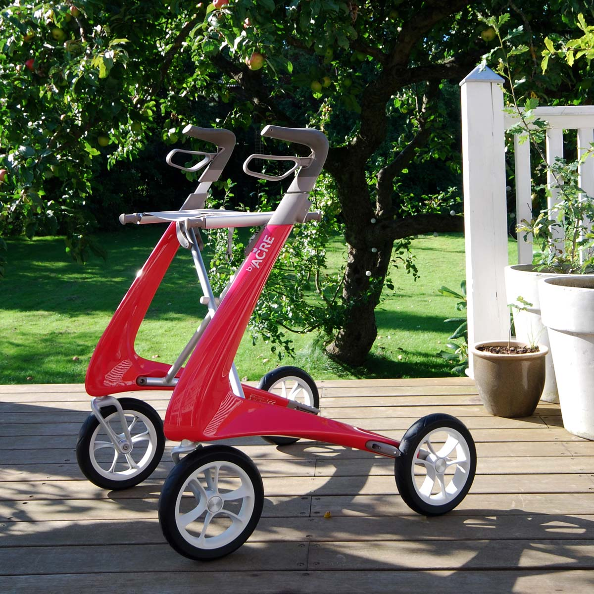 Red Carbon Ultralight Rollator byACRE - seen in perspective on a patio in a garden